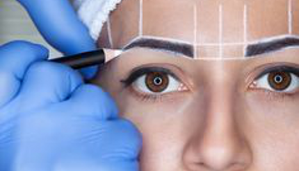 Female getting stencil drawn on her eyebrows for shape