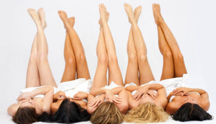 Waxing females laying down with smooth legs in the air after being waxed