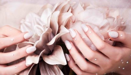 Hand with white nails holding rose pink flowers