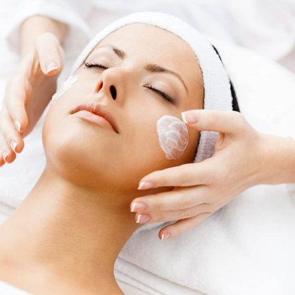 Female with lotion on her face about to receive a face treatment