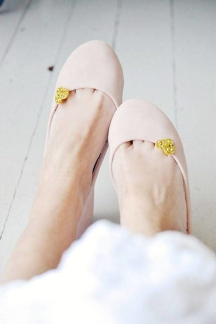 Feet wearing pink shoes with a yellow flower attached to it