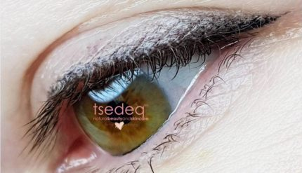 Close up of a brown and green eye with white eye shadow and a watermark in the pupil