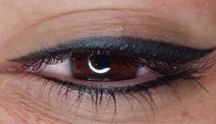 Closeup of a brown eye with long black eye lashes with light reflecting off it