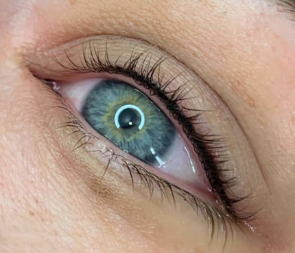 Closeup of a blue eye with long black eye lashes with light reflecting off it