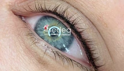 Close up of a blue eye with white eye shadow and a watermark in the pupil