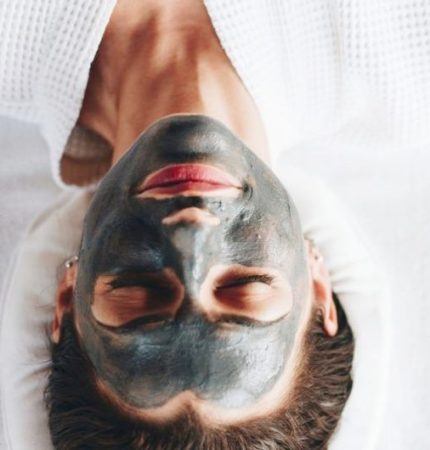 Woman receiving charcoal facial treatment